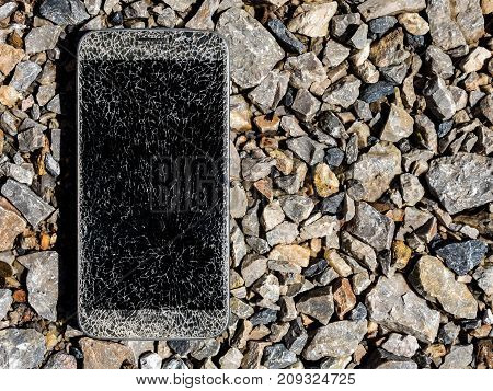 Close-up image of old broken and cracked screen smartphone drop down on gravel with copy space
