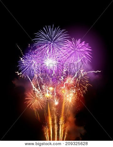 A large bright fireworks display event with golden orange and purple rocket breaks.