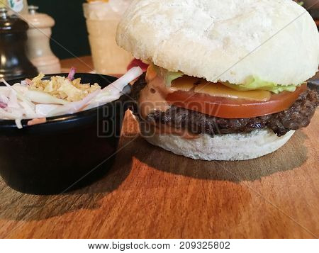 Burger with Coleslaw Salad on Wooden Table Background at the Restaurant. Tasty fast food meal, freshly made from natural organic meat and baked ciabatta with tomato, cheese, sause and green salad.