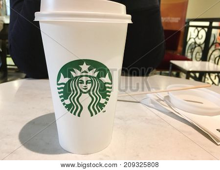 MOSCOW, RUSSIA - OCTOBER 9, 2017: Starbucks Coffee on White Table at the Coffee Shop Background. Take away paper cup of famous Starbucks Coffee with company logo in the middle and empty copy space.