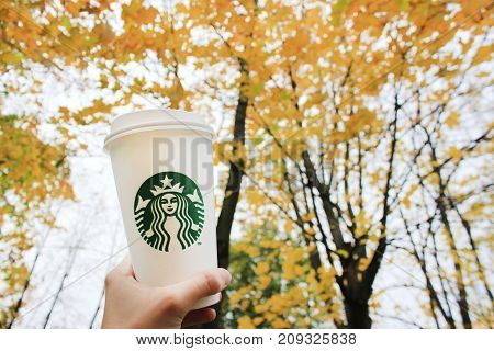 MOSCOW, RUSSIA - OCTOBER 9, 2017: Person Holding in Hand To Go Cup of Starbucks Coffee on Autumn Background. Paper White Starbucks Coffee Cup against colorful orange tree leaves during autumn season.