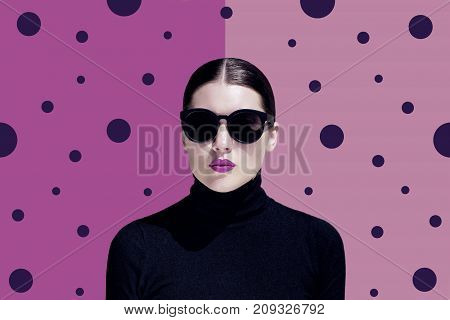 Fashion portrait of a young woman with black sunglasses and bright painted lips wearing black sweater next to a bright colorful background.