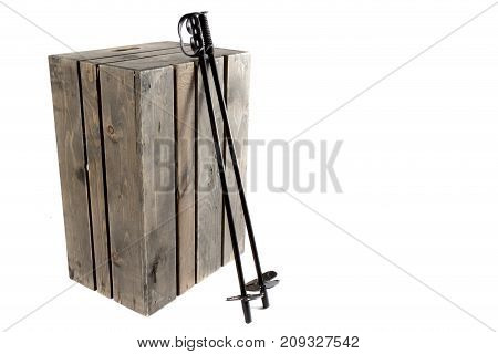 Ski poles and a wooden crate isolated on a white background