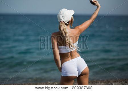 Beautiful blonde girl in sportwear on the beach makes selfie.