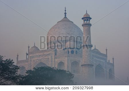 View of Taj Mahal in early morning fog Agra Uttar Pradesh India. Taj Mahal was designated as a UNESCO World Heritage Site in 1983.