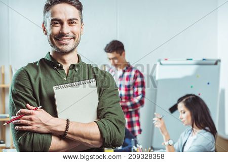 handsome young student holding notebook and smiling at camera