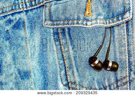 Earphones in pocket denim jacket. Ear headphones on a jeans background