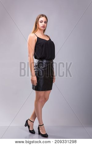 Portrait of a plus size female model posing in black dress over grey background. Beautiful woman with curvy figure. poster