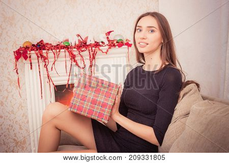 Happy brunette woman holding christmas gift with red tinsel sitting on couch near fireplace at home