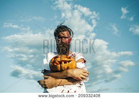 Halloween Hipster Man Holding Pumpkin On Blue Sky
