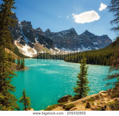 Beautiful sunny day at Moraine lake in Banff National Park, Alberta, Canada, with snow-covered peaks of canadian Rocky Mountains in the background.