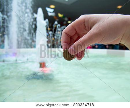 A man tosses a coin into a fountain
