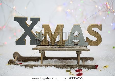 x-mas written letters on sled glowing background