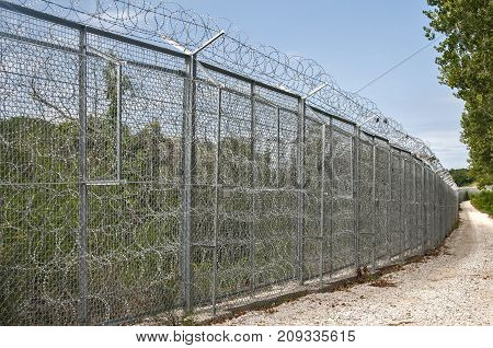 Border fence closeup with wire mesh closeup on nature and blue sky background