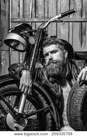 Bearded man hipster biker brutal male with beard and moustache in leather jacket sits on floor near motorcycle with auto wheel tire or tyre on wooden background