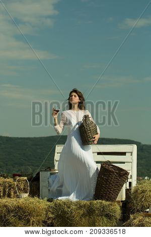 Woman with glass of wine wicker bottle and basket. Winery tour concept. Girl in white dress posing on blue sky. Summer vacation holidays and celebration. Model with alcohol drink on sunny day.