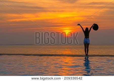 Smilling asina woman happy in big hat relaxing on the swimming pool travel near the sea and beach in the sunset. Summer Concept