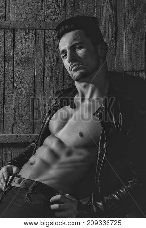 Handsome sexy sensual muscular stylish young man in leather jacket with bare torso sitting indoor on wooden background vertical picture