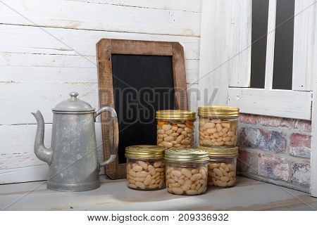 jars of delicious white Tarbais beans with chalkboard near the window