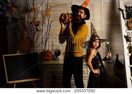 Wizard And Little Witch In Hats Hold Candlestick And Pumpkin