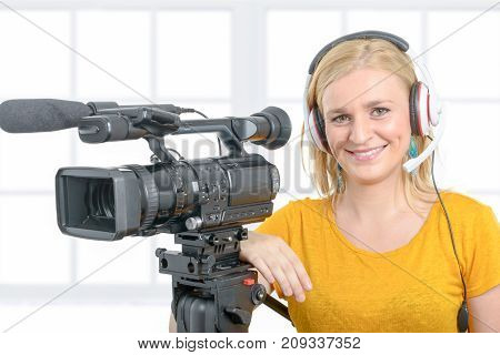 a smiling young woman in yellow t-shirt with professional camcorder on white