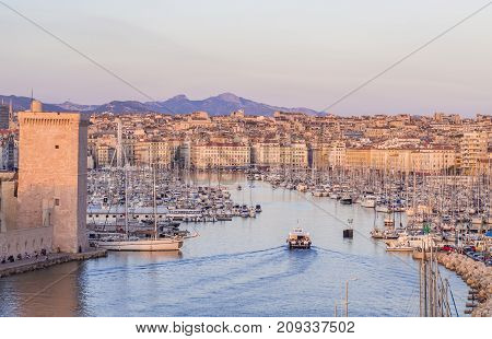 MARSEILLE FRANCE - AUGUST 07 2017: The old Vieux Port of Marseille beneath Cathedral of Notre Dame France at sunset.