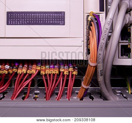 Network cables connected to switch - close up of data center hardware. Multi colored wires.