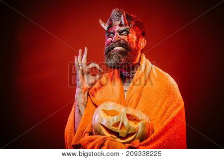 Halloween Man Devil Hold Pumpkin On Red Background