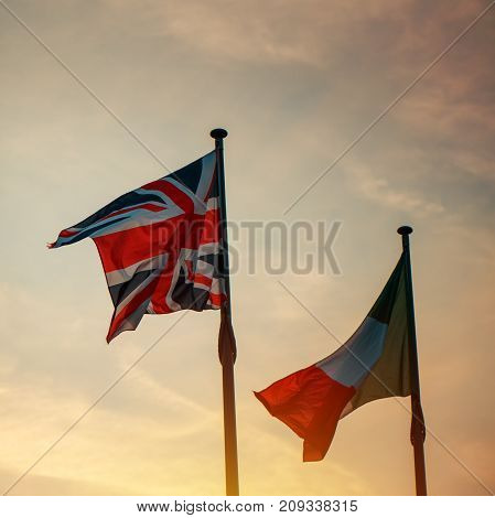 Italian and British flag on a pole in sunset two national banners of Italy and United Kingdom (Great Britain) waving in the wind.