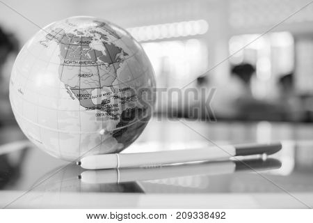 Earth globe model America maps in Global ball put on Tablet with stylus pen for learning in teacher desks in high school students blur background white black tone. Geography subject of learning.