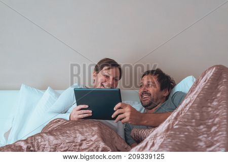 Happy couple husband and wife in bedroom using personal electronics devices