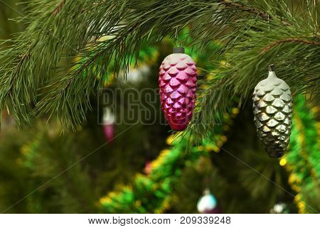 Two vintage glass Christmas ornaments - purple and silver with patina fir cones - on a background of a blurred Christmas tree