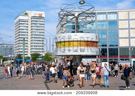 BERLIN, GERMANY -  AUGUST 08, 2017: Tourists and residents at the world clock at the Alexanderplatz in Berlin-Mitte