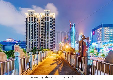 TAICHUNG TAIWAN - JULY 17: View of a footbridge and modern architecture in the downtown area of Taichung at night on July 17 2017 in Taichung