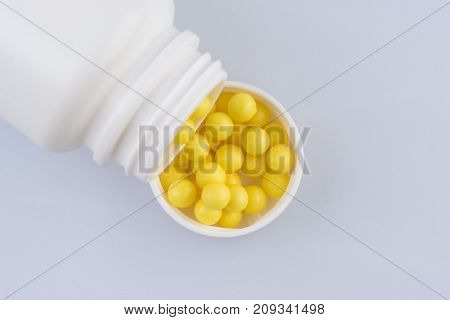 Container with the pills vitamins on the grey medical table