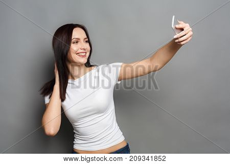 Everyday confidence. Beautiful woman taking selfie with phone on gray studio background, copy space