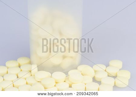 Transparent container with scattered pills closeup on the grey medical table