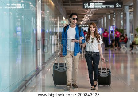 Asian couple traveler walking with suitcases in modern an airport travel and transportation concept.motion style