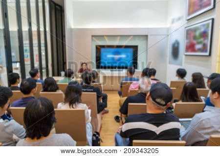 Abstract blurred photo of seminar or meeting room with speakers on the stage and attendee background