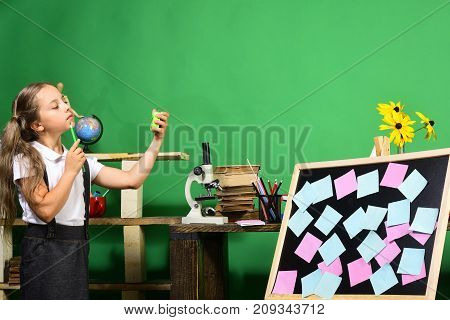 Schoolgirl With Proud Face In Classroom. Girl Holds Green Clock