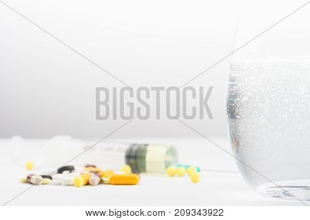 Glass of water syringe and pills on the table with area for text on the left top