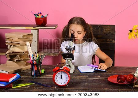 Girl Sits At Desk With Stationery, Clock, Books And Flowers