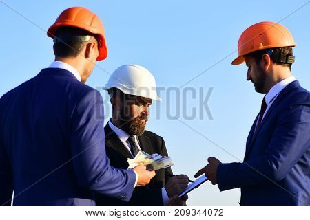 Board Of Architects With Interested Faces In Suits And Helmets