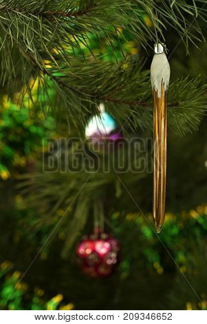 vintage glass Christmas ornament - bronze or golden icicle - on a background of a blurred Christmas tree
