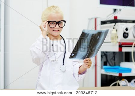 Cute little radiologist with x-ray result looking at camera in hospital