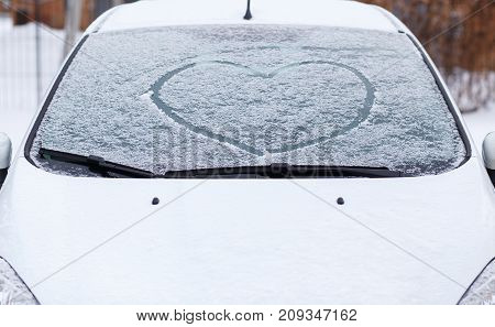 Heart love symbol on windscreen of car in snow. Front view of snowy car after winter blizzard