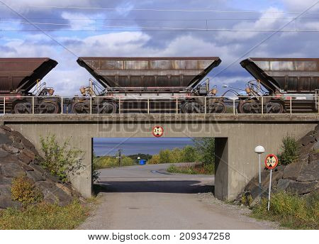 Bridge and a road passes under the Ore Line. Power lines above. Sign this side.