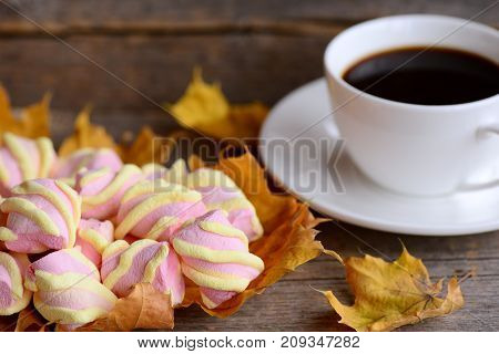 Fluffy sweet marshmallow candy on a plate, a cup of coffee, yellow leaves on a wooden table. Fall breakfast or snack concept. Rustic style. Closeup