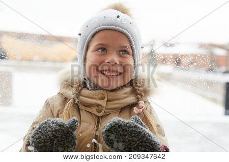 Curious little girl in winterwear staring at something behind window