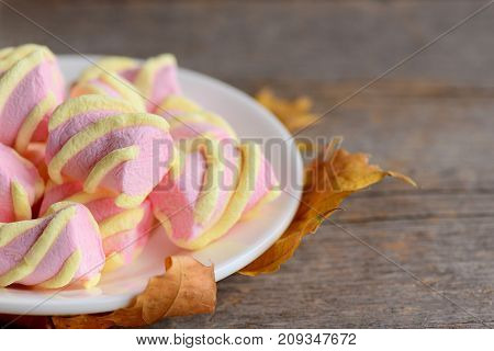 Colorful mini marshmallows on a plate. Fall leaves. Vintage wooden background with copy space for text. Heap of tasty marshmallow closeup
